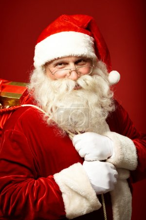 Photo for Portrait of happy Santa Claus holding sack with gifts and looking at camera - Royalty Free Image