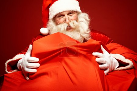 Photo for Portrait of Santa Claus embracing huge red sack with gifts - Royalty Free Image