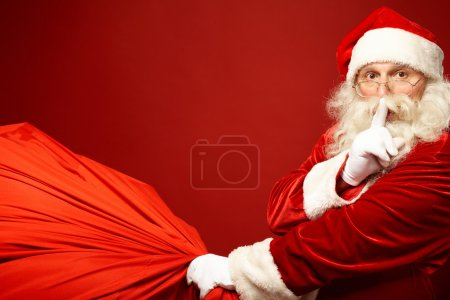 Photo for Portrait of Santa Claus with huge red sack keeping forefinger by his mouth and looking at camera - Royalty Free Image