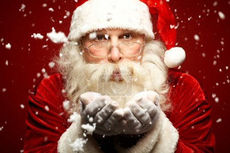Photo for Photo of Santa Claus in eyeglasses blowing snow and looking at camera - Royalty Free Image