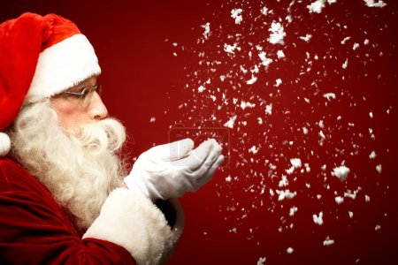 Photo for Photo of Santa Claus blowing snow and looking at it - Royalty Free Image