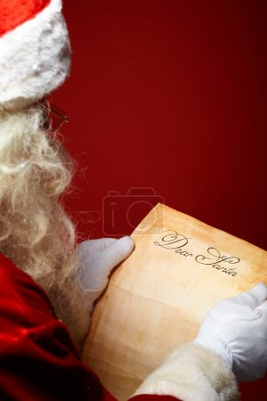 Photo for Image of Santa Claus reading Christmas letter in his hands - Royalty Free Image