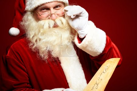 Photo for Portrait of happy Santa Claus holding Christmas letter in his hands and looking at camera - Royalty Free Image