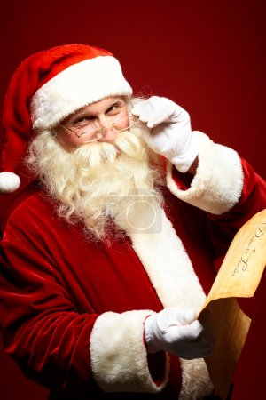 Photo for Portrait of happy Santa Claus holding Christmas letter and looking at camera - Royalty Free Image