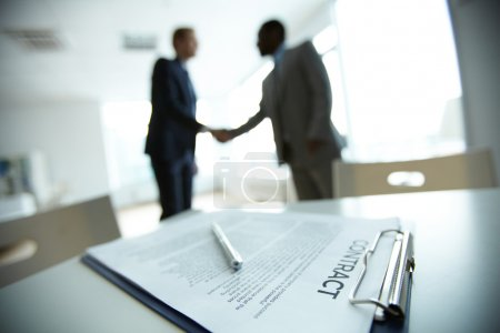 Photo for Image of business contract on background of two employees handshaking - Royalty Free Image