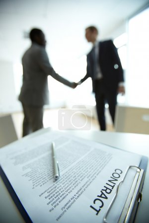 Image of business contract on background of two em...