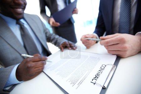 Photo pour Image d'homme d'affaires, signature du contrat avec deux employés près de - image libre de droit