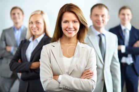 Photo pour Portrait d'une femme d'affaires souriante regardant la caméra avec quatre employés derrière - image libre de droit