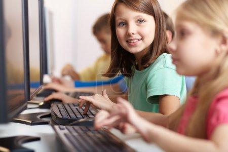 Photo pour Portrait de belle écolière regardant la caméra tout en tapant à la leçon - image libre de droit