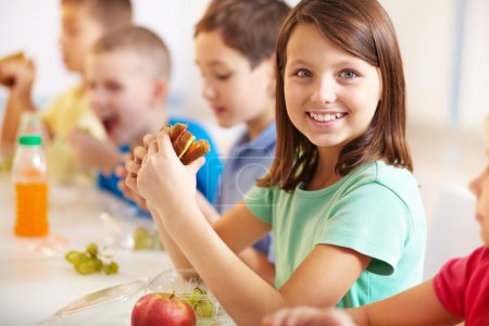 Photo for Group of classmates having lunch during break with focus on smiling girl with sandwich - Royalty Free Image