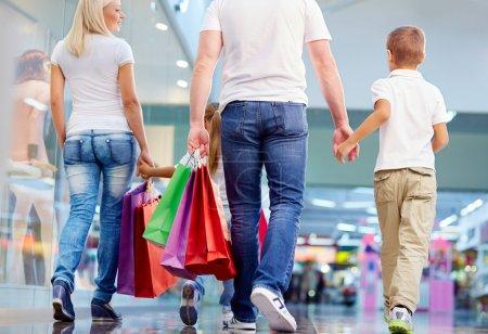 Photo pour Vue arrière de la famille avec des sacs en papier marchant dans le centre commercial - image libre de droit