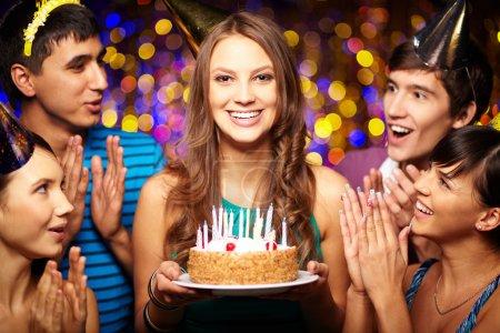 Foto de Retrato de muchacha alegre celebración de pastel de cumpleaños rodeado de amigos en el partido - Imagen libre de derechos
