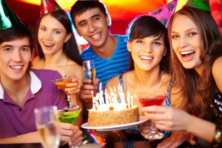 Photo for Portrait of joyful friends toasting and looking at camera at birthday party - Royalty Free Image
