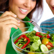 Close-up of young couple eating vegetable salad fr...
