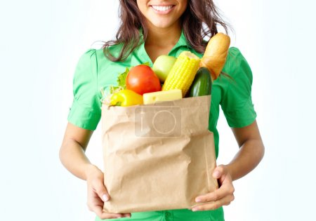 Photo for Image of paper packet full of different fruits and vegetables held by female - Royalty Free Image
