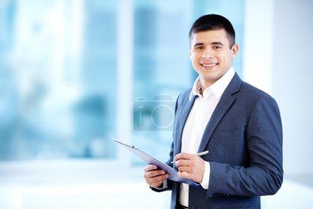 Photo pour Portrait d'homme d'affaires gaie des notes et regardant la caméra - image libre de droit