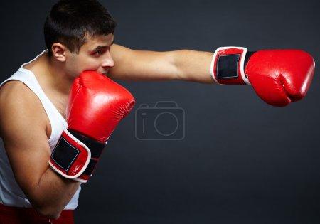 Photo pour Portrait de jeune homme en gants de boxe rouges combat isolément - image libre de droit