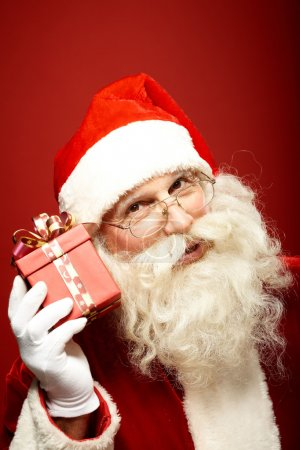 Photo for Photo of Santa Claus holding red giftbox by his ear - Royalty Free Image