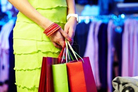 Photo pour Image de mains de shopaholic avec trois sacs à provisions - image libre de droit