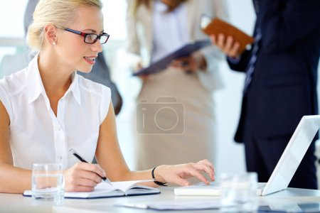Photo for Portrait of busy secretary looking at laptop while networking - Royalty Free Image