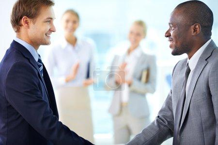 Photo pour Portrait d'hommes d'affaires confiants poignée de main et leurs collègues applaudissant sur fond - image libre de droit