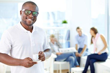 Foto de Retrato de tipo africano feliz con copa mirando a cámara en ambiente de trabajo - Imagen libre de derechos