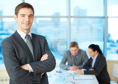 Photo for Image of cross-armed leader looking at camera in working environment - Royalty Free Image