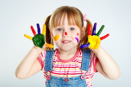 Photo for Girl having fun, her face and palms covered with paint - Royalty Free Image