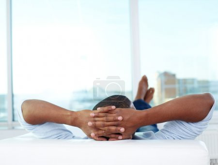 Photo for Image of young African man lying on sofa and having rest - Royalty Free Image