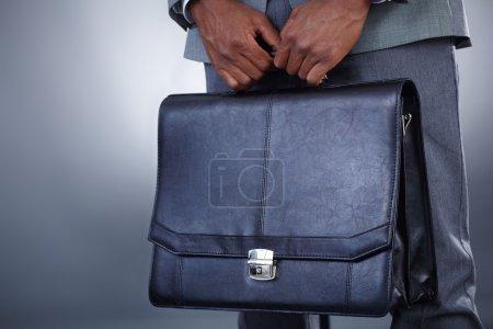Photo pour Gros plan de l'homme d'affaires avec mallette à la main isolé sur fond gris - image libre de droit