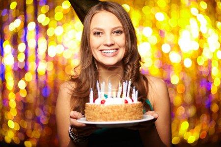 Photo pour Portrait de fille joyeuse tenant gâteau d'anniversaire et regardant la caméra à la fête - image libre de droit