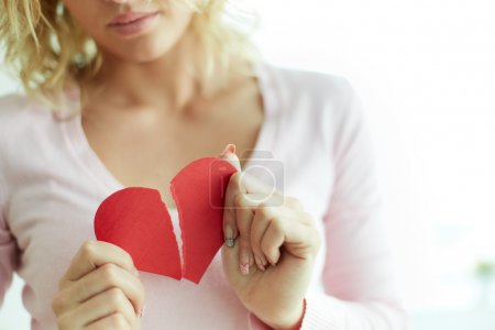 Photo for Close-up of female showing red broken paper heart - Royalty Free Image