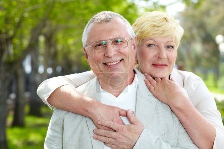Photo for Portrait of happy mature woman hugging her husband outside - Royalty Free Image
