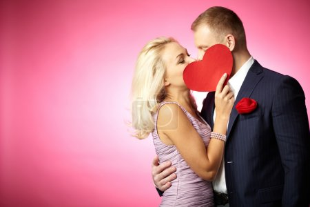 Photo for Two young dates kissing behind paper heart - Royalty Free Image