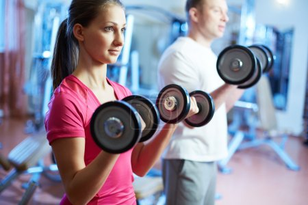 Photo for Portrait of pretty girl training in gym with young man near by - Royalty Free Image