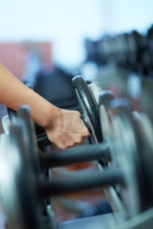 Photo for Image of female hand taking barbell from row of barbells in gym - Royalty Free Image