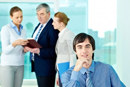 Photo for Portrait of confident leader looking at camera with working employees behind - Royalty Free Image