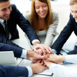 Image of business partners making pile of hands at...