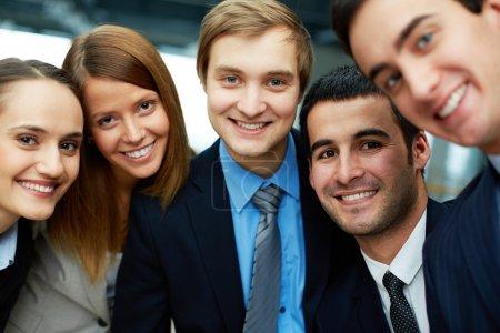 Photo pour Portrait de cinq partenaires regardant la caméra avec des sourires - image libre de droit