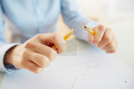 Photo for Stressed business worker releasing tension by breaking a pencil - Royalty Free Image