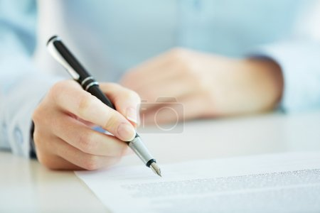 Photo for Business worker signing the contract to conclude a deal - Royalty Free Image