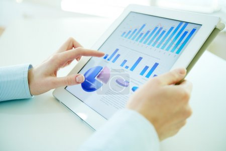 Photo for Business person analyzing financial statistics displayed on the tablet screen - Royalty Free Image