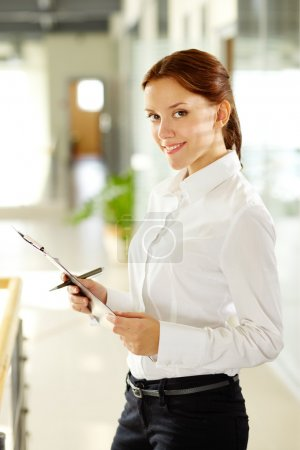 Photo for Young businesswoman with document looking at camera and smiling - Royalty Free Image