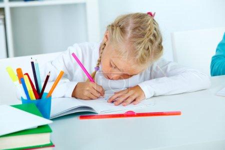 Photo pour Diligent élève dessin dans son cahier d'exercices - image libre de droit
