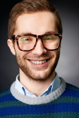 Photo pour Portrait d'homme séduisant dans des lunettes regardant la caméra avec le sourire - image libre de droit