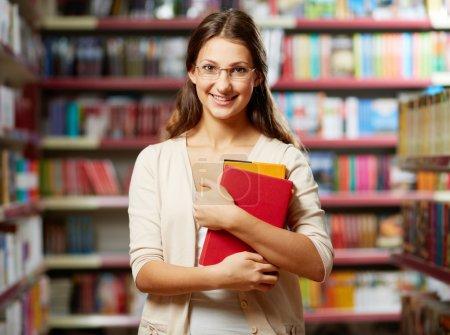Photo pour Portrait d'un étudiant intelligent avec des livres dans la bibliothèque du Collège - image libre de droit