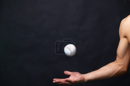 Photo for Image of male arm playing with baseball ball over black background - Royalty Free Image