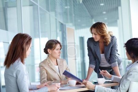 Photo pour Image de quatre femmes discutant de plan d'affaires à la réunion - image libre de droit