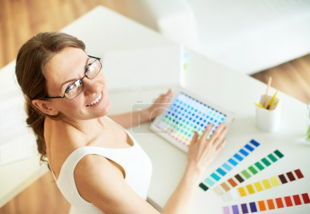 Happy female designer looking at camera at workplace