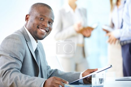 Photo for Portrait of a cheerful business worker smiling at the camera - Royalty Free Image